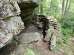 A stone walled shelter built up against a cliff face alongside the Loyalsock Trail.